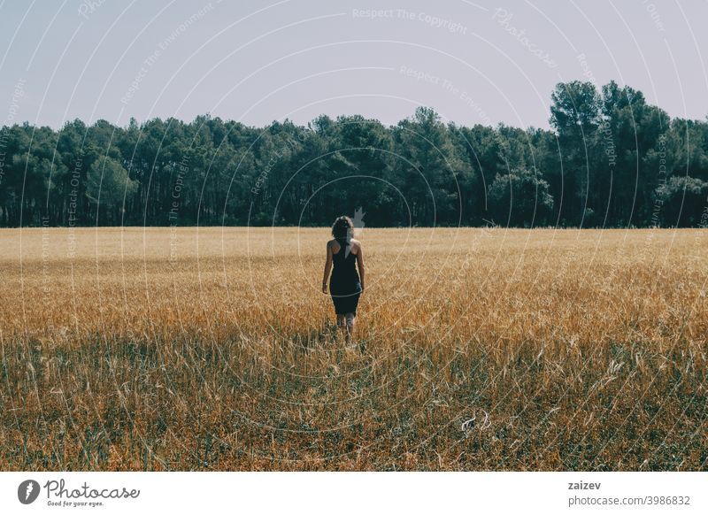 girl walking through a beautiful yellow field horizontal peace tranquility produce growth golden land light outside color image idyllic panoramic path scenics