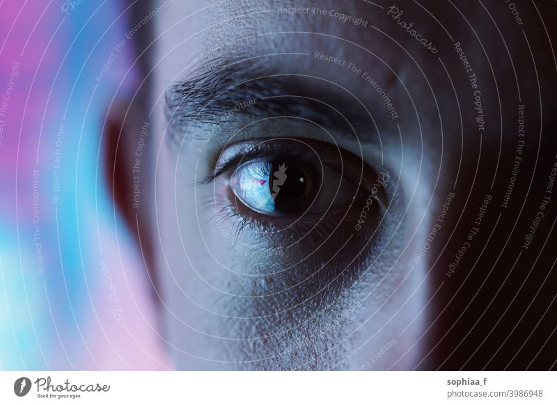 Expressive look - closeup of an eye with blurred blue and pink neon light background and high contrast disco light man color close up expression nightlife