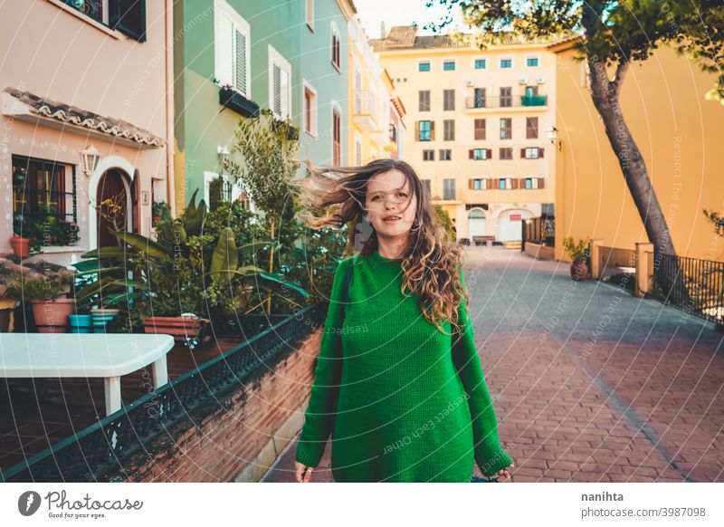 Young woman wearing green oversize sweater enjoying a windy day in a colorful city travel portrait lifestyle model europe european blonde female outdoors free