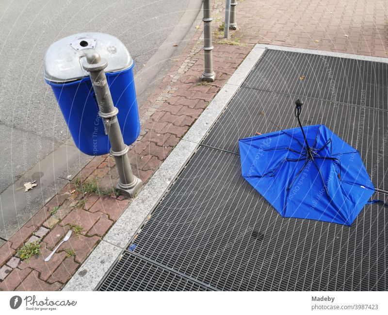 Blue garbage home next to and blue umbrella on the ventilation grille of a subway station at the Senckenberganlage in the Westend of Frankfurt am Main in Hesse, Germany