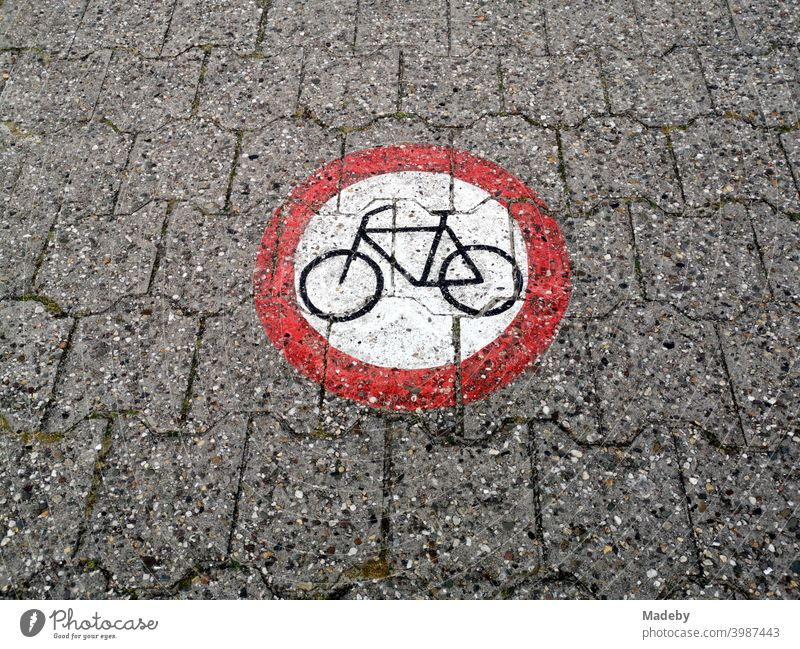A round traffic sign painted on the composite pavement prohibits the passage of bicycles on the dyke at the harbour of Neuharlingersiel near Esens in East Frisia in the district of Wittmund in Lower Saxony