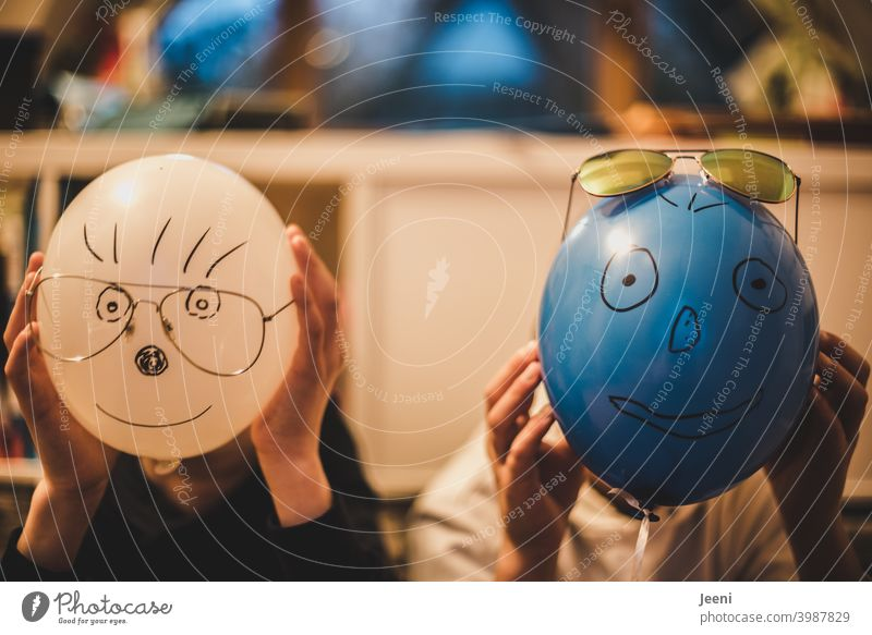 Balloons painted with funny faces in front of the heads of two children | Painted eyes, nose, mouth, hair and attached glasses | Hands hold the balloon tightly