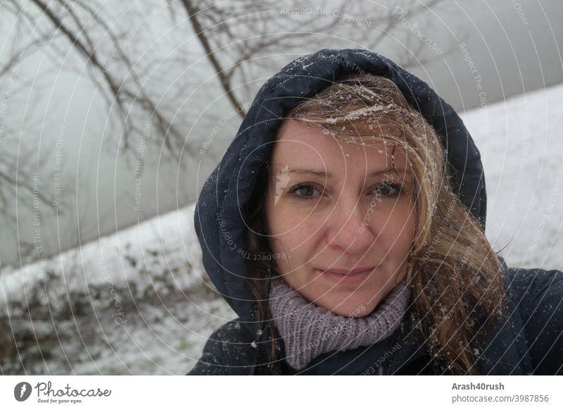 Junge Frau im Schneefall mit Kapuze sportlich bewegung erholung Kalt Winter Schneeflocken