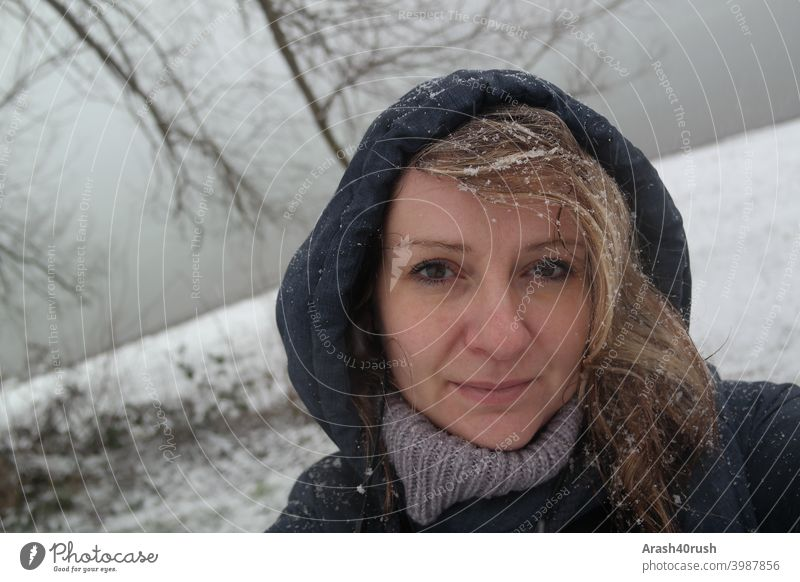 Young woman in snowfall with hood (self-portrait) Athletic Movement Relaxation Woman Cold Winter snowflakes eyes Nose Mouth long hairs Blonde blue jacket