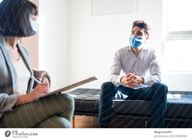 Psychologist talking with patient on therapy session. psychologist professional notes mental health face mask therapist psychotherapy psychology doctor