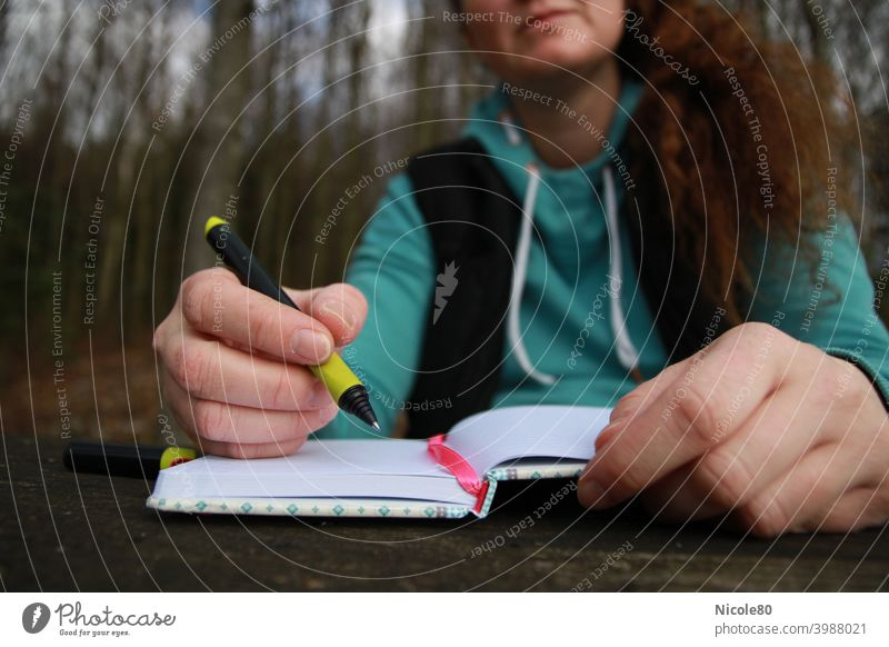 Writing woman in nature Write Woman Nature Notebook hands Forest Inspiration Wooden table hoodie Sweater thinking Diary