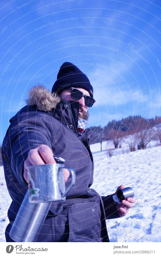 The tea pouring model, young man with sunglasses in the snow, teapot and mug in hand. Lifestyle Leisure and hobbies Outdoors Class outing Young man Landscape