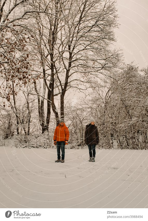 Retired couple in winter landscape To go for a walk Winter Snow chill trees Bushes Woman Man Couple annuity Pensioners relax Relaxation Stand View to the side