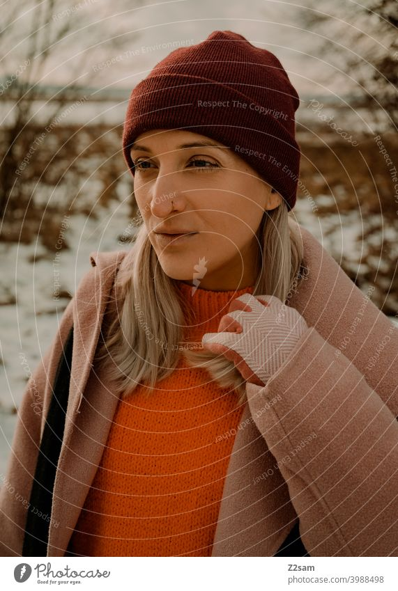 Portrait of a fashionably dressed woman in winter landscape Winter wonderland Woman Young woman Coat To go for a walk Snow Sun Light Nature Landscape Scarf Cap