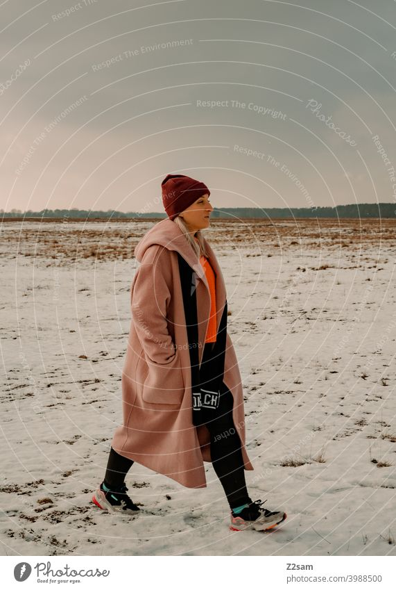 Fashionably dressed young woman goes for a walk stroll Winter wonderland Woman Young woman Coat To go for a walk Snow Sun Light Nature Landscape Scarf Cap