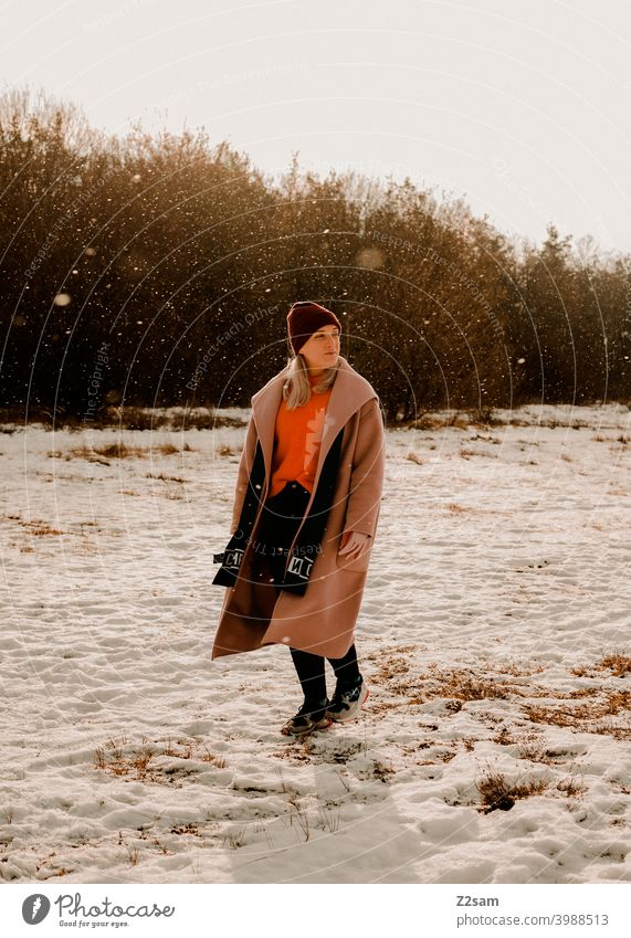 Fashionably dressed young woman walking in light snowfall stroll Winter wonderland Woman Young woman Coat To go for a walk Snow Sun Light Nature Landscape Scarf