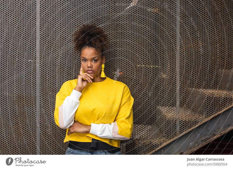 Trendy black woman in bright outfit fashion color yellow style trendy model earring accessory young confident female african american curly hair ethnic afro