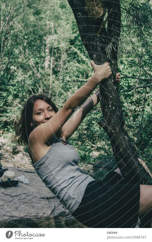 girl hanging from a tree laughing agility humor tranquility youth vitality person happiness smiling one person young adult joy playing expression looking