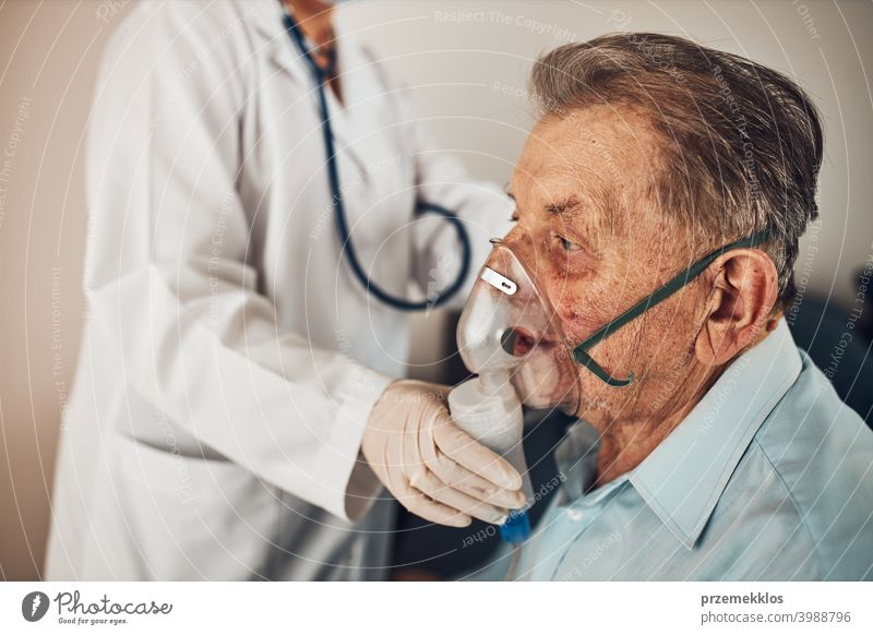 Doctor applying a medicine during inhalation to senior man suffering from lung disease. Covid-19 or coronavirus treatment patient person hospital medical