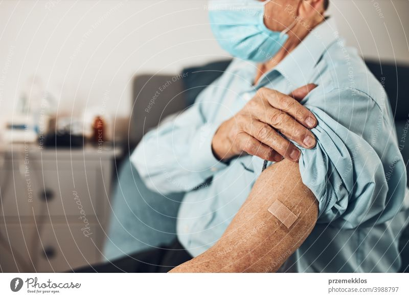 Senior man patient holding shirt sleeve up with a plaster in place of injection of vaccine. Covid-19 or coronavirus vaccination person hospital senior medical