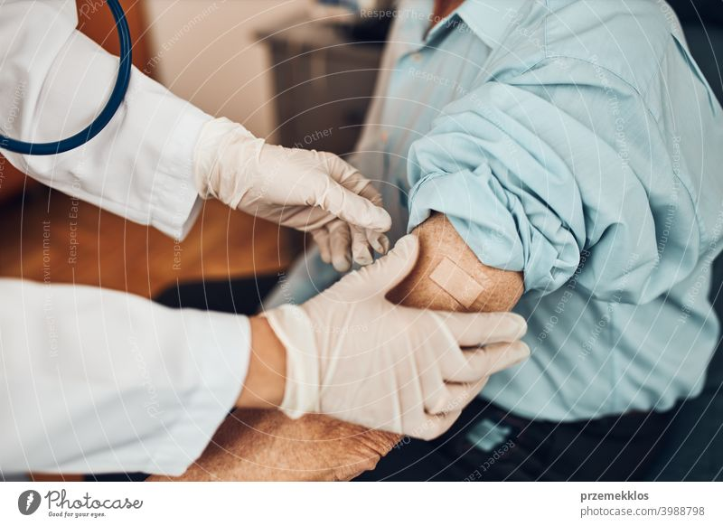 Doctor putting a plaster in place of injection of vaccine to senior man patient. Covid-19 or coronavirus vaccination person hospital doctor medical medicine