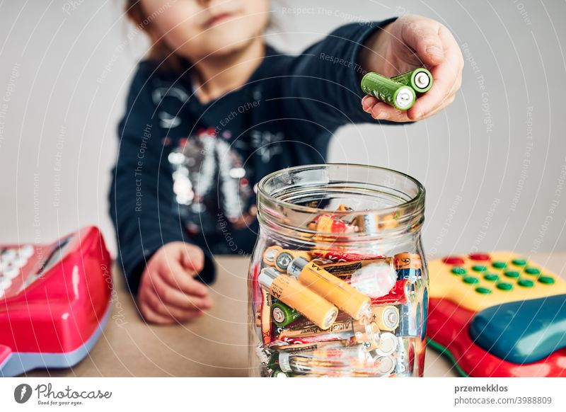 Little girl putting used batteries into jar for recycling. Child separating waste person environmental conceptual responsibility power recycle save throw