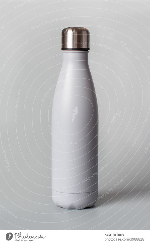 Grey reusable bottle on grey background monochrome mockup insulated ecologic water steel thermo aluminum blank close up concept copy space negative space