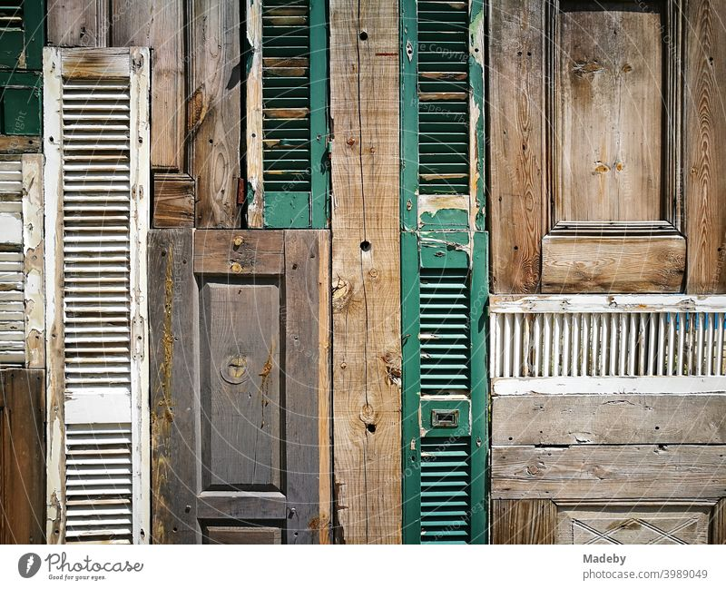 Decorative wall of old wooden doors and shutters in an open-air bar in the old town of Alacati on the Mediterranean Sea near Izmir in Turkey background Wood