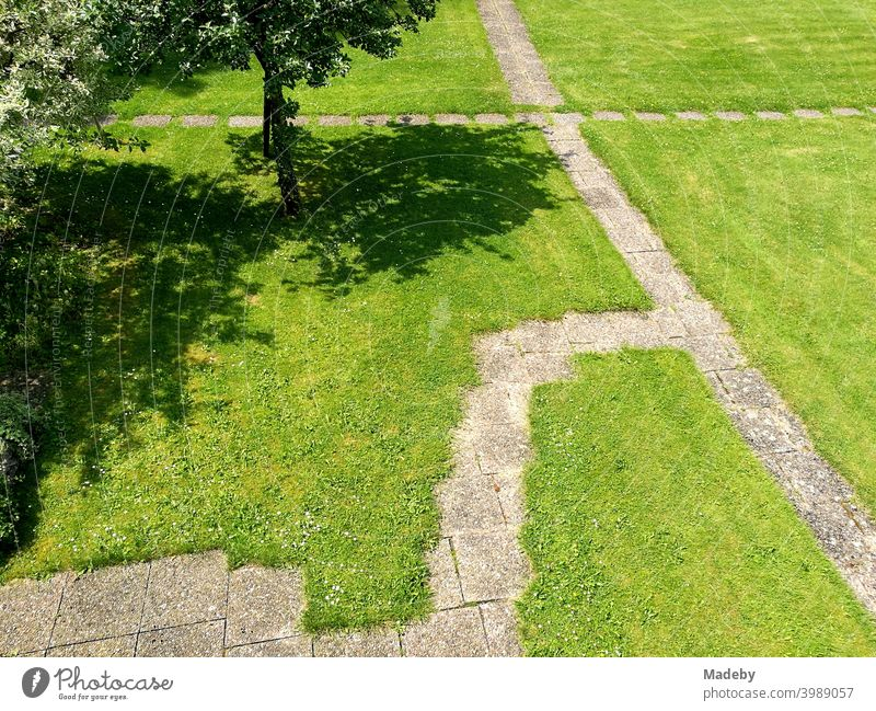 Garden gnomes with stone slabs on green lawn in a park-like garden in summer sunshine in Oerlinghausen near Bielefeld in the Teutoburg Forest in East Westphalia-Lippe
