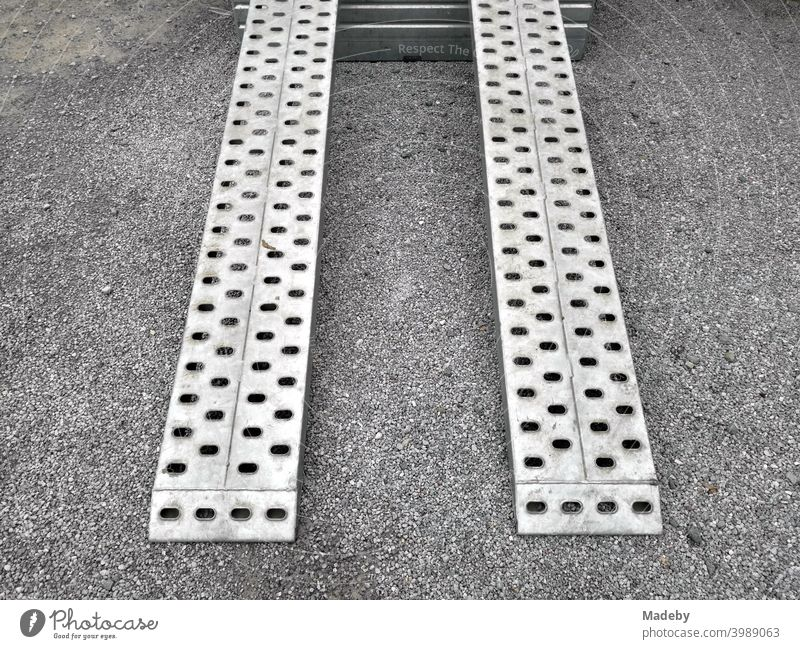 Ramp made of perforated plate of a car trailer for transporting small construction machinery on grey gravel in Helpup near Oerlinghausen in the Teutoburg Forest in East Westphalia-Lippe, Germany