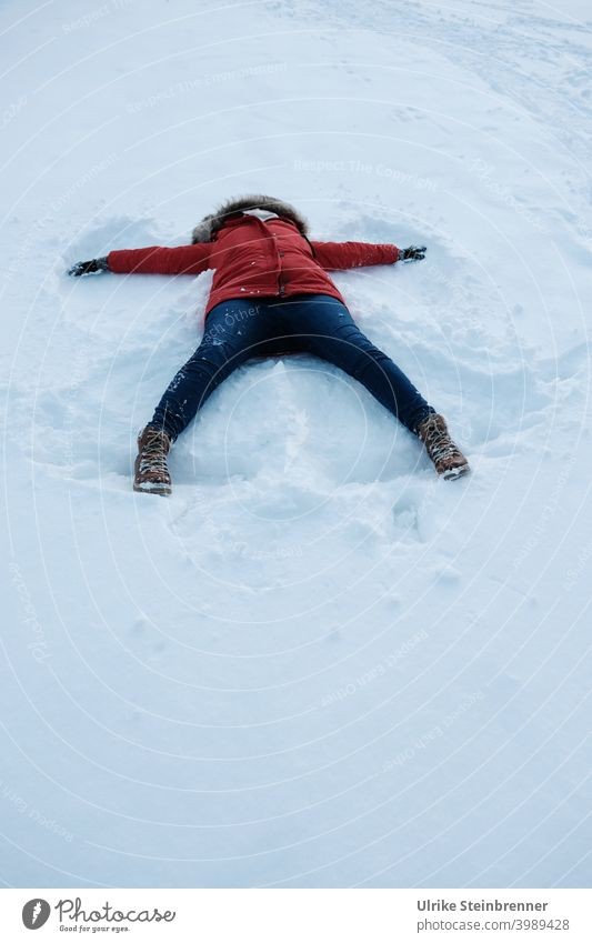 Woman in red anorak makes a snow angel Snow Winter fun snow angels Anorak Virgin snow winter fun Angel angel wings Imprint Meadow Snow layer White Cold