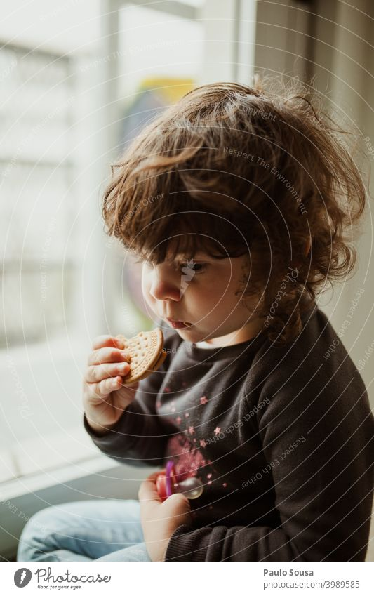 Cute little girl eating cookie Child childhood Cookie Eating thinking Colour photo Infancy Human being kid Delicious Joy Authentic Caucasian Calm