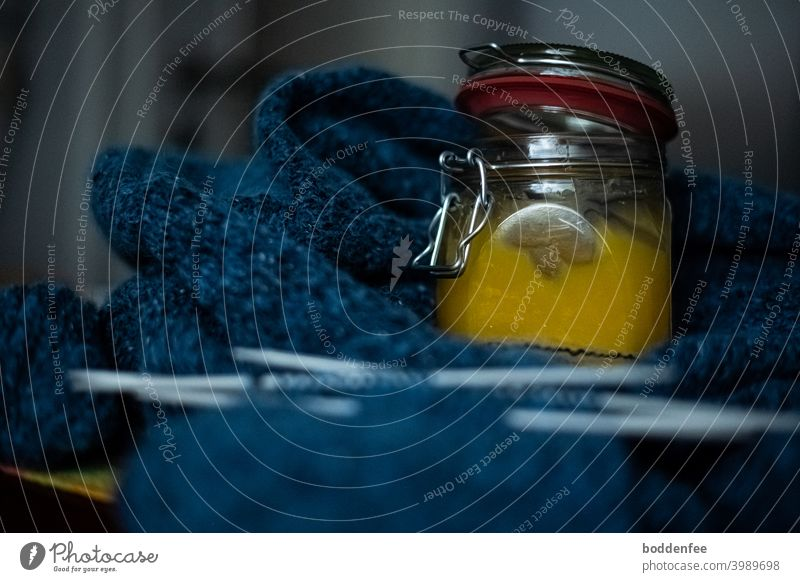 A filled honey jar stands as nerve food on a blue knitted work, focused on the jar with blurred foreground and background Knit Handcrafts Wool Knitting needles