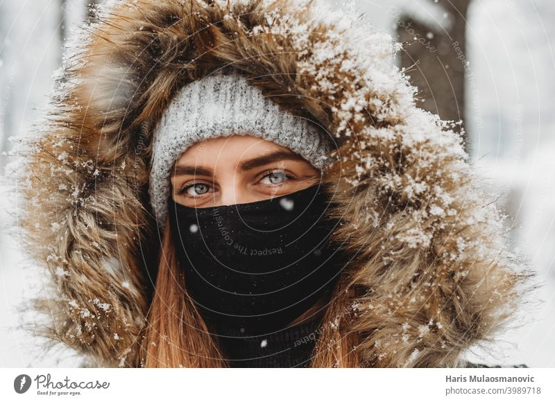 Beautiful woman with facial mask outdoors in snow attractive beautiful beauty caucasian close up cold cute enjoy snow enjoy winter eyes face face mask fashion