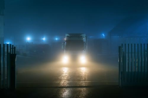 Truck leaving a factory at night on a very foggy day with poor visibility. truck lights darkness front view mist gate transportation large city door abstract