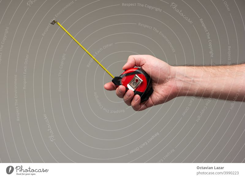Caucasian male hand holding a measuring tape ruler isolated on gray background man home gesture metric construct diy build caucasian carpentry concept building
