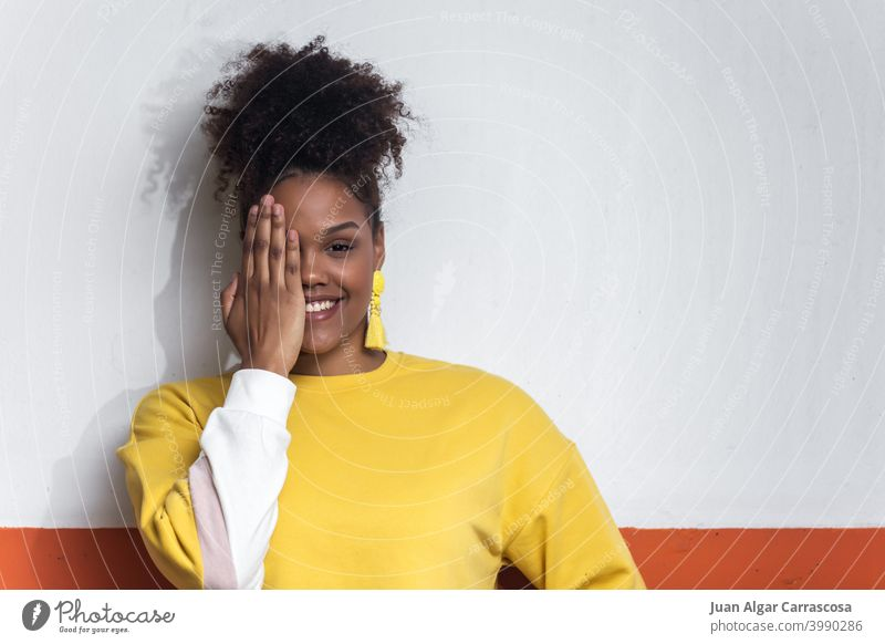 Smiling black woman in yellow outfit covering eye with hand style color trendy cover face cheerful hide bright smile young female african american ethnic