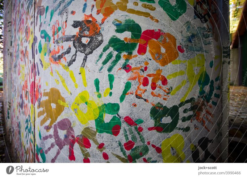 Hand in hand designed wall Street art Imprint Many Creativity Teamwork Participation Play of colours Multicoloured Abstract Agreed Silhouette