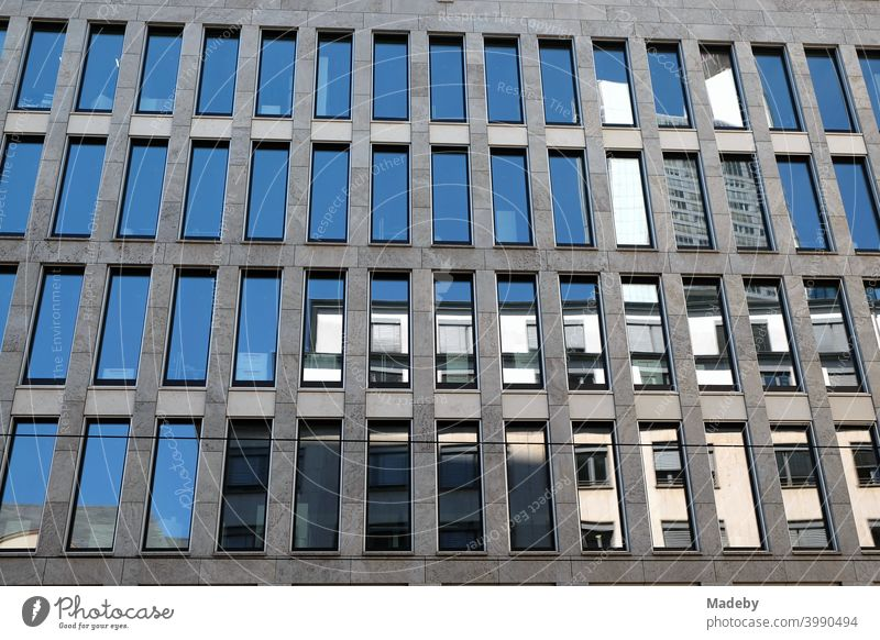 Reflecting blue windows in grey concrete of a modern office building in summer sunshine in the city of Frankfurt am Main in Hesse, Germany Architecture Facade