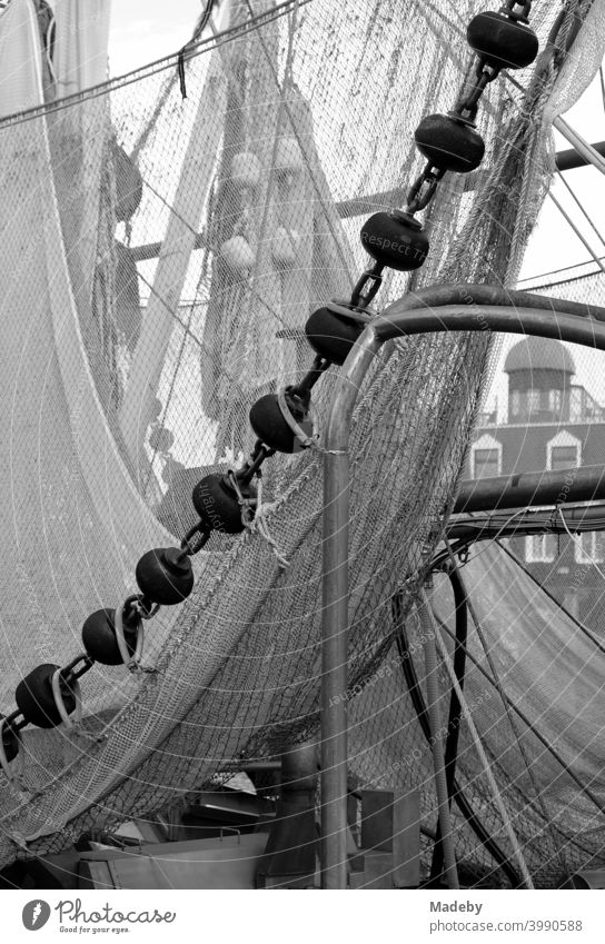 Fishing nets of an old fishing cutter in the harbour of Neuharlingersiel at the North Sea coast near Esens in the district of Wittmund in Lower Saxony, photographed in classic black and white
