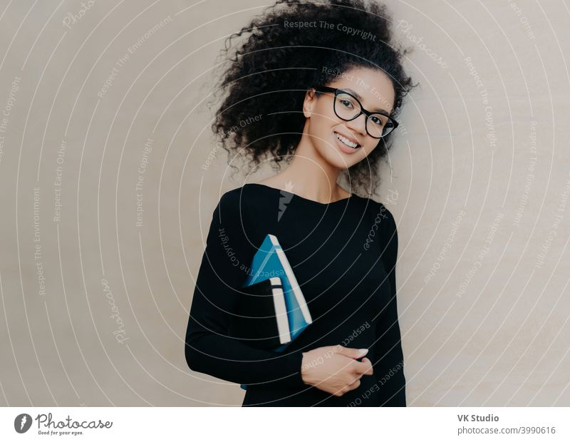 Positive curly African American student carries notepad and diary, wears black clothes, transparent glasses, enjoys studying in university, isolated on grey background. Cute woman with notebook