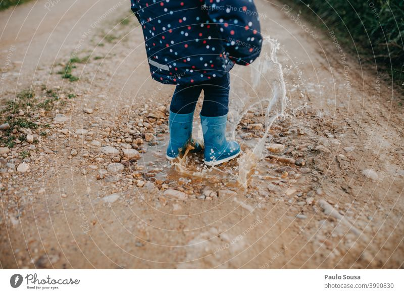 Child with red rubber boots playing on a puddle Puddle Rubber boots Winter Rain Water Wet Human being Exterior shot Colour photo Playing Joy Boots Dirty Mud