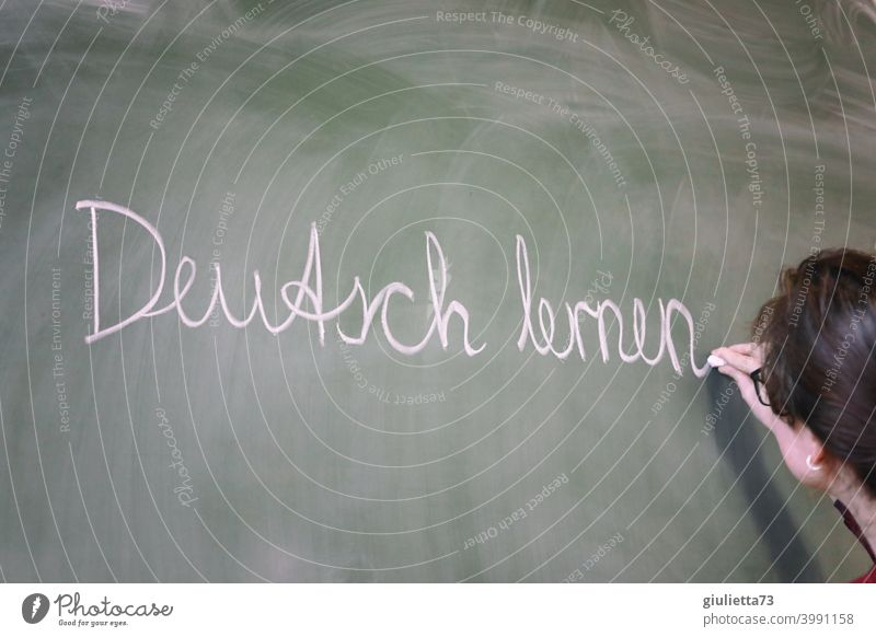 Learning German - Young teacher writes with chalk on the blackboard, lessons Forward-looking incorporation integrate sb. Living together Society Adult Education