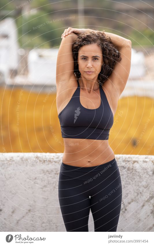 Middle-aged woman with fitness body working out on the terrace of her house training workout 40s middle age sportswear lifestyle person female healthy exercise