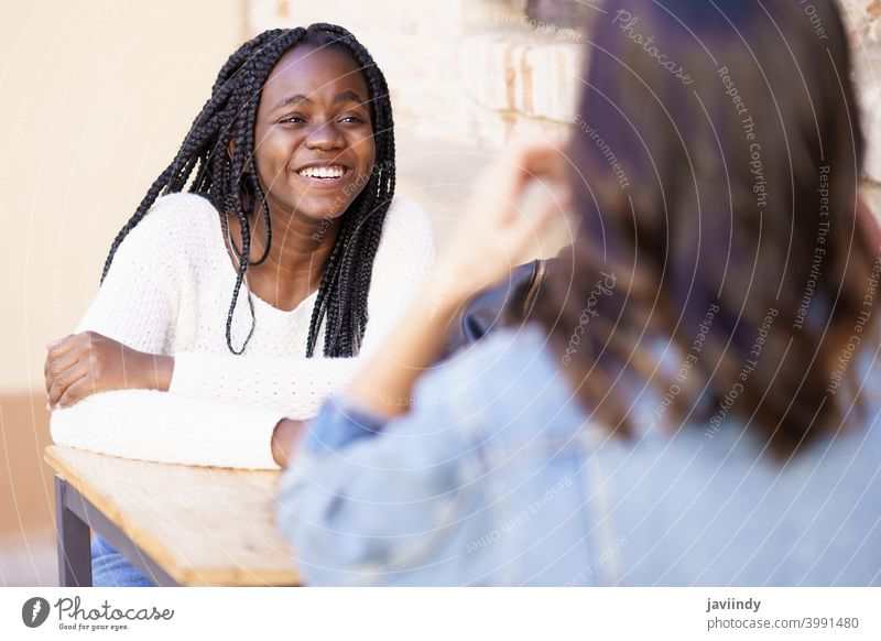 Two multiethnic friends talking sitting at a table outside a bar. woman outdoors multiracial happiness girl friendship happy smile young beautiful lifestyle