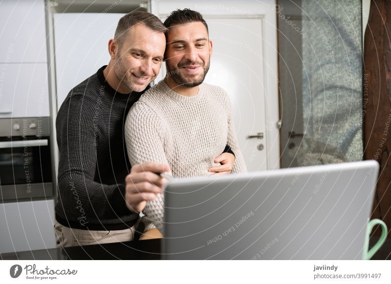 Romantic Gay couple working together at home with their laptops. gay men teleworking hug homosexual hugging lgbt lgbtq male relationship boyfriend people 30s