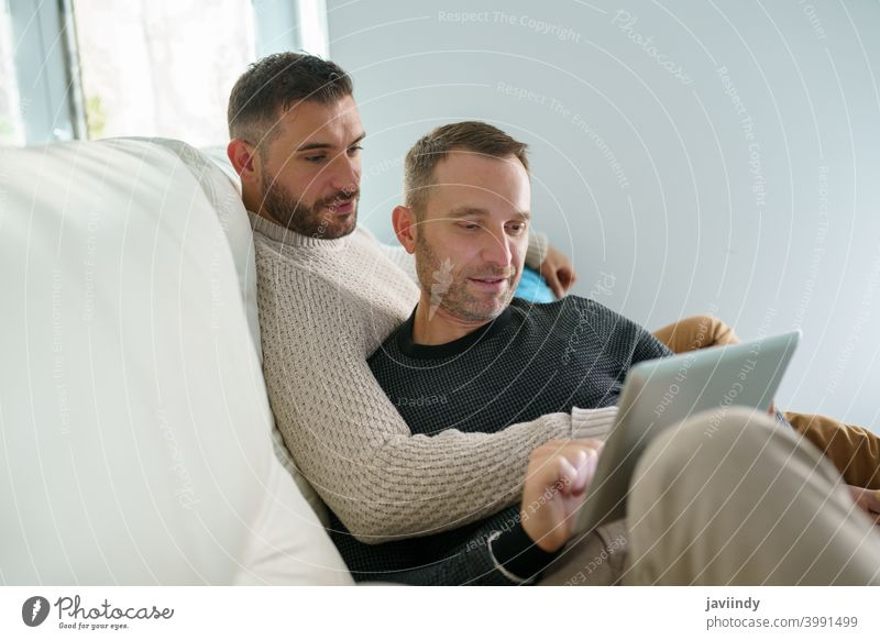 Gay couple consulting their travel plans together with a digital tablet. gay men homosexual lgbt lgbtq male relationship boyfriend people 30s togetherness man