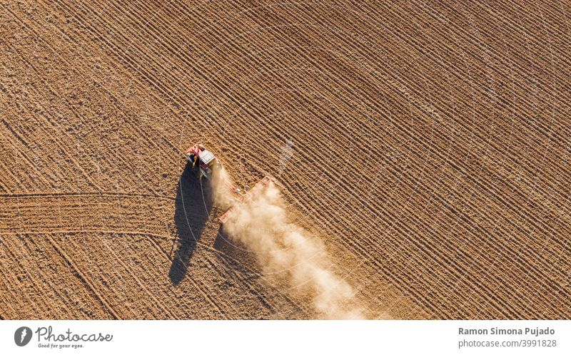Aerial drone view of a tractor tilling the land overhead view Tractor tractors brown farming Farm Equipment fields drone photography dust rural rurally