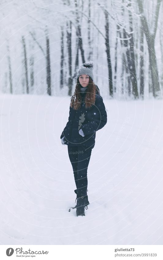 Portrait of teenage girl in winter snowfall standing in a snowy park Front view Looking into the camera portrait Girl teenager Colour photo Youth (Young adults)