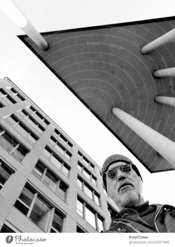 An old man stands between two skyscrapers and looks at the sky Man Face Eyeglasses Looking Facial hair Head portrait Architecture Building City