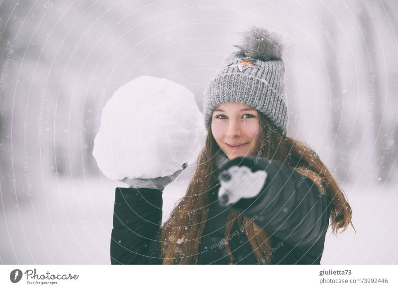 Happy naughty teen girl in winter with huge snowball Winter Snow White Bobble hat Feminine Subdued colour snowflakes snowy Long-haired 13 - 18 years