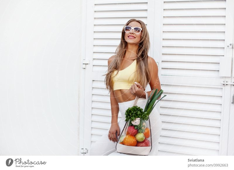 A young girl in sunglasses and sportswear stands in the background of the door with a bag full of vegetables and fruits. The concept of healthy eating and healthy lifestyle