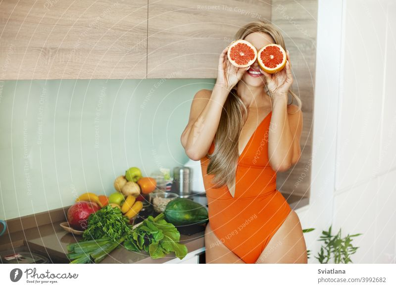 Portrait of a sporty girl with a grapefruit in her hands in the kitchen with fresh vegetables and fruits. The concept of a healthy lifestyle, health, beauty