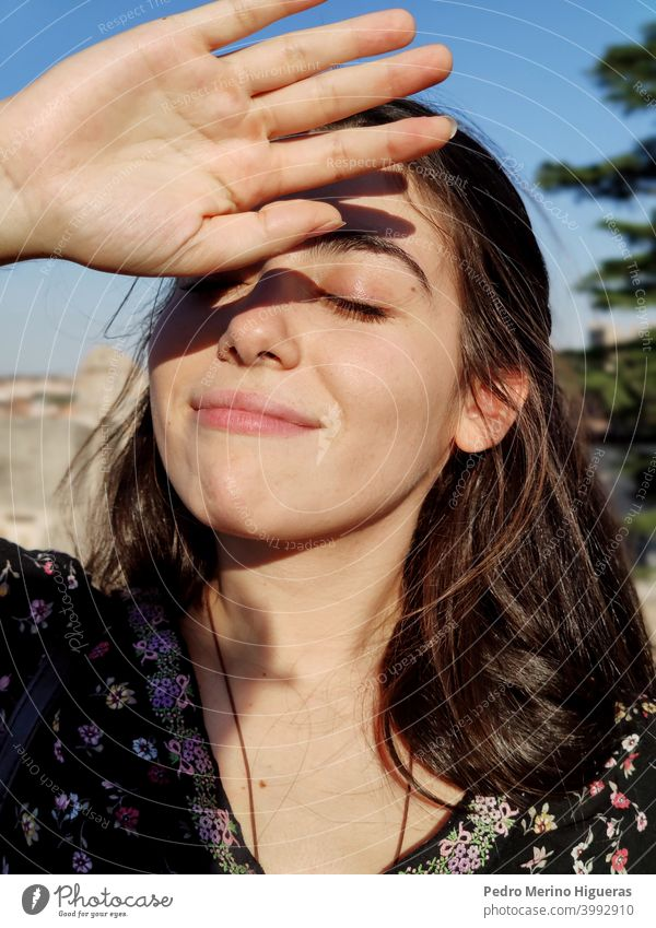 Girl with the eyes closed covering the sun with her hand. health dermatology female treatment worried sunshine hot facial summer wrinkle skin bright sunblock