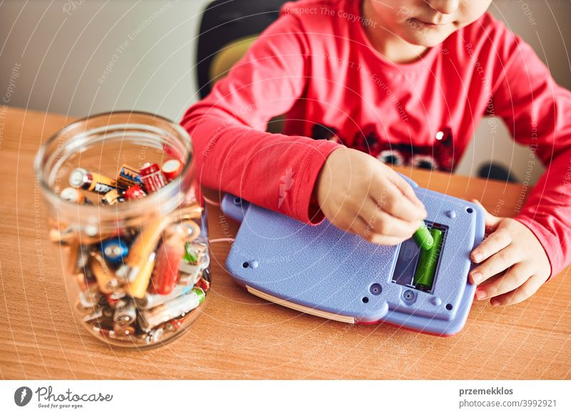 Little girl removing used batteries from toy and putting into jar for recycling battery bin child collecting concept conceptual determination dispose earth